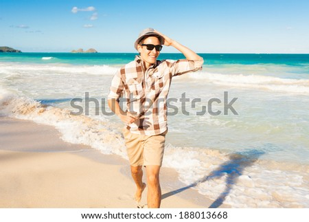 Handsome young man running on a sandy beach. - stock photo