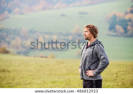 Handsome young man running outside in autumn nature, resting