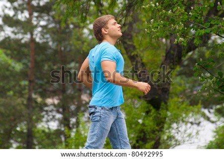 Handsome young man running through park - stock photo