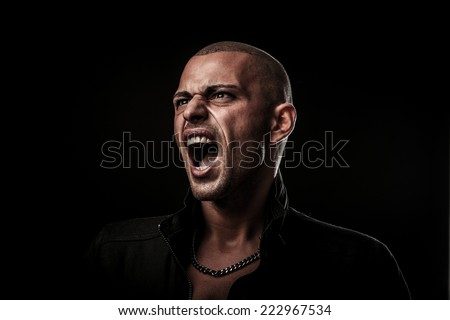 Handsome young man screams into a copy space as a sign of freedom of speech - stock photo