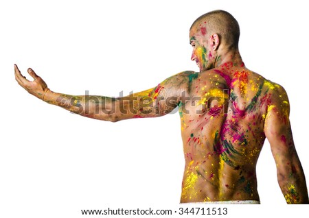 Handsome young man seen from the back with skin all painted with Holi colors, isolated on white background, arm stretched out