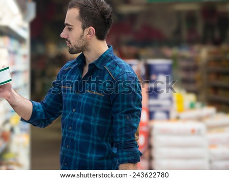 Handsome Young Man Shopping In A Grocery Supermarket - stock photo