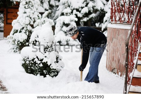 Handsome young man shoveling snow in the yard  - stock photo