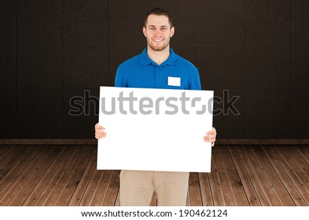 Handsome young man showing card against dark room with floorboards - stock photo