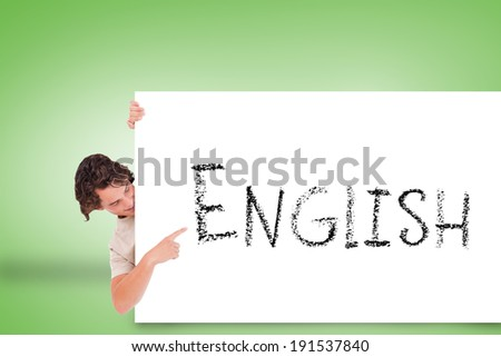 Handsome young man showing card with english against green background - stock photo
