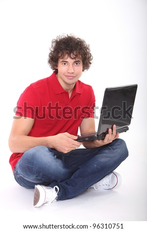 Handsome young man sitting and holding laptop - stock photo