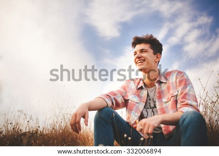 Handsome young man sitting and smiling on sky background. Attractive caucasian teenage boy wearing shirt laughing and looking confident with copy space. - stock photo