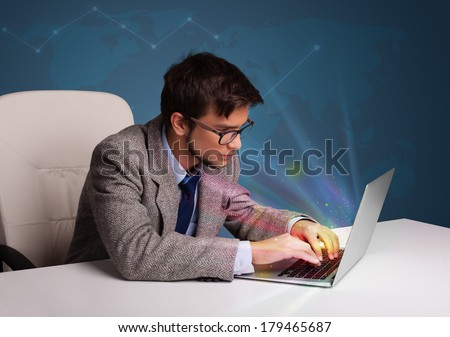 Handsome young man sitting at desk and typing on laptop with abstract lights