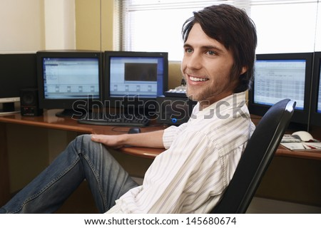 Handsome young man sitting at desk in front of computers - stock photo