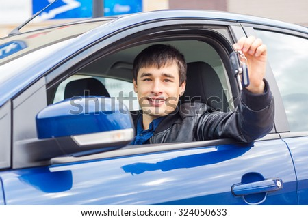 Handsome young man sitting in his new car with a car key