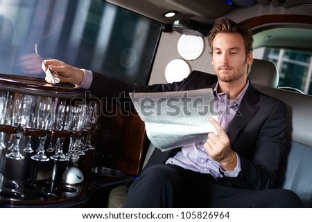 Handsome young man sitting in limousine, reading newspaper. - stock photo
