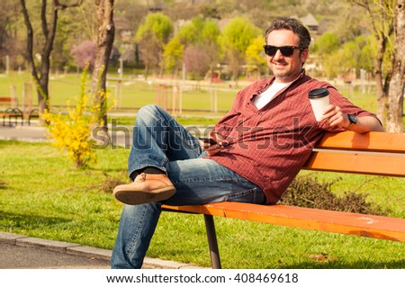 Handsome young man sitting in park on wooden bench smiling and enjoying a coffee - stock photo