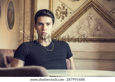 Handsome young man sitting in vintage retro elegant place in Europe, looking at camera - stock photo