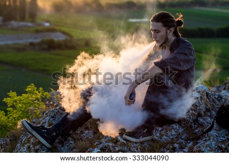 Handsome young man sitting on a rocks and smoking electronic cigarette at outdoors. - stock photo