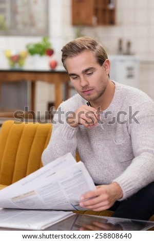 Handsome young man sitting on a sofa in his living room reading a newspaper - stock photo