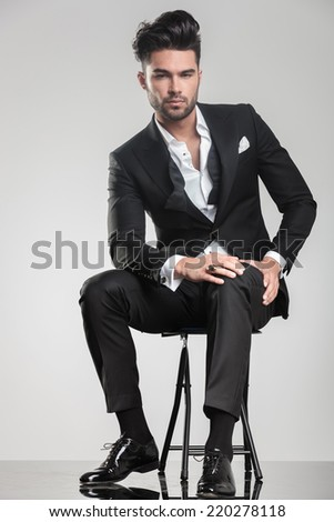 Handsome young man sitting on a stool, holding one hand on his knee while looking at the camera. - stock photo