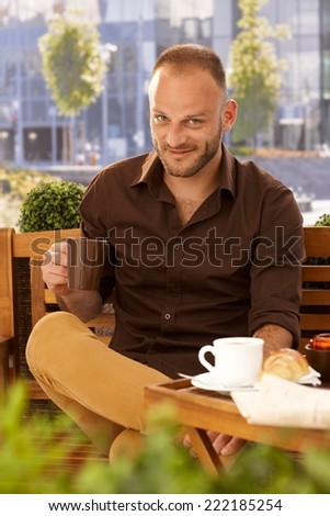 Handsome young man sitting on bench in outdoors cafe, having breakfast, smiling happy, looking at camera. - stock photo
