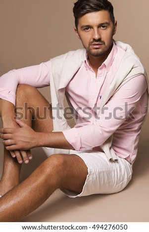 Handsome young man sitting on floor and looking at camera at the background studio and casual style