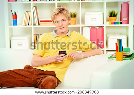 Handsome young man sitting on sofa at home and talking on the phone. - stock photo
