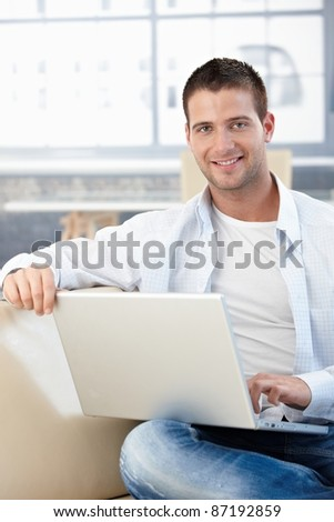 Handsome young man sitting on sofa at home, using laptop.? - stock photo