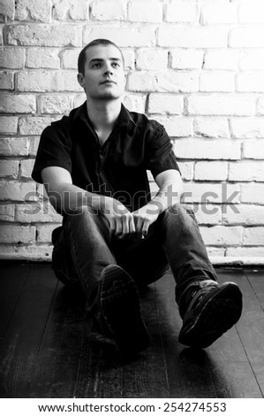 Handsome young man sitting on the floor near the white brick wall, toned black and white