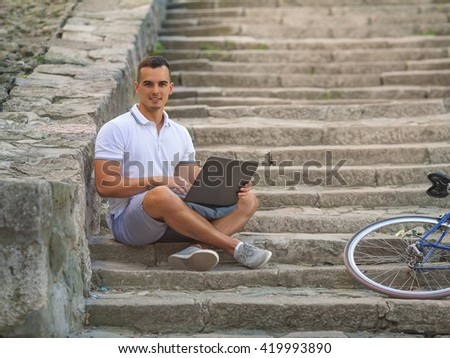 Handsome young man sitting on the outdoor stairs and using laptop while his bicycle is beside him - stock photo