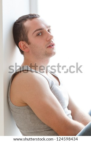Handsome young man sitting on windowsill, wearing in grey singlet and jeans. Natural light
