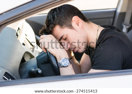 Handsome Young Man sleeping in a Car, resting head on wheel
