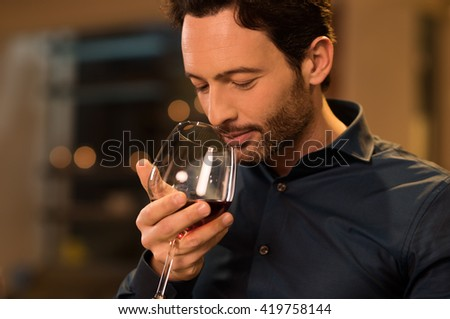 Handsome young man smelling red wine before drinking it. Young man drinking red wine in a luxury restaurant. Handsome young man tasting a glass of red wine during dinner. - stock photo