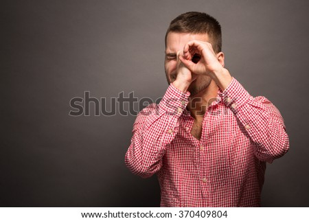 Handsome young man smiling and making binocular or tube with his hands isolated over grey background. - stock photo