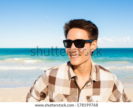 Handsome young man smiling on the beach. - stock photo