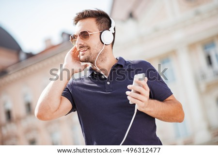 Handsome young man smiling while listening to music in the city.