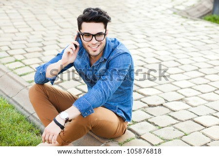 handsome young man smiling while talking on a smart-phone outdoors - stock photo