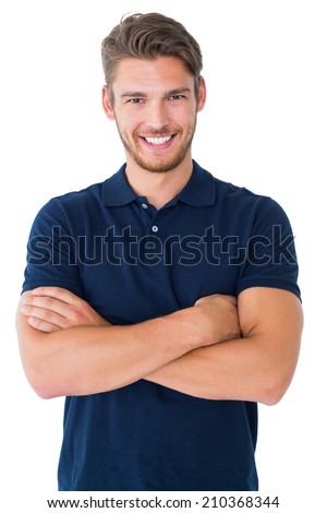 Handsome young man smiling with arms crossed on white background - stock photo