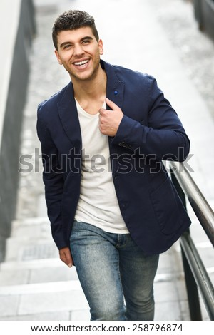 Handsome young man smiling with blue eyes in the street. Model of fashion walking in urban background wearing white t-shirt, jeans and blue jacket - stock photo