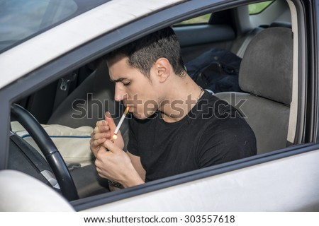 Handsome Young Man smoking cigarette while Driving a Car