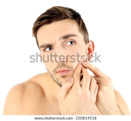 Handsome young man squeezing pimple isolated on white - stock photo