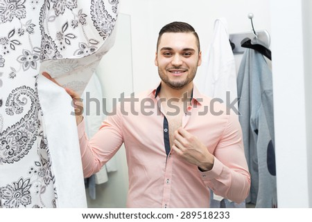 Handsome young man standing at boutique changing cubicle