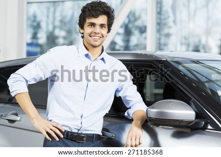 Handsome young man standing besides car in showroom  - stock photo