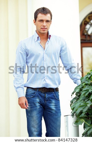 Handsome young man standing in front of his house outdoors - stock photo