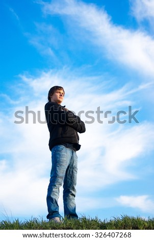 Handsome young man standing in the field and looking at sunset