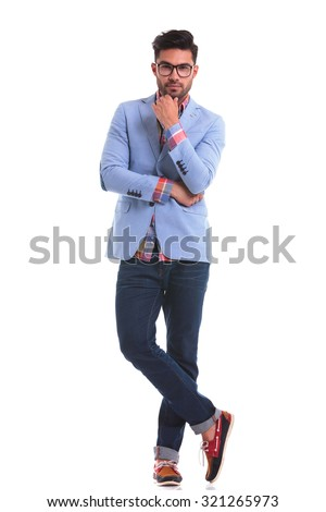 Handsome young man standing on studio background looking at the camera while holding his hand to the chin.