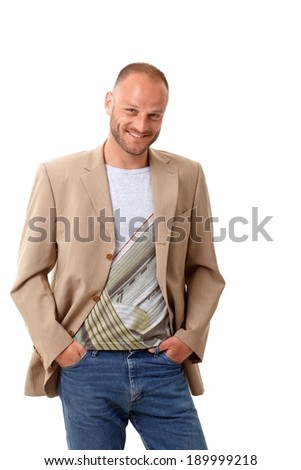 Handsome young man standing over white background with hands in pockets, smiling, looking at camera. - stock photo