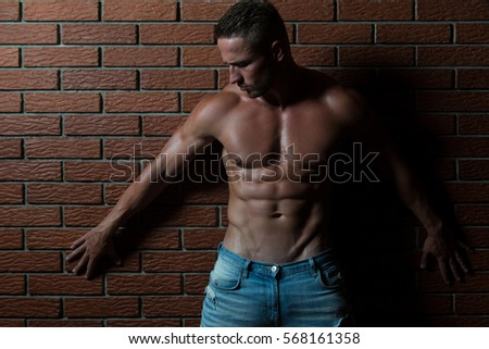 Handsome Young Man Standing Strong In The Gym And Flexing Muscles - Muscular Athletic Bodybuilder Fitness Model Posing After Exercises On Wall of Bricks