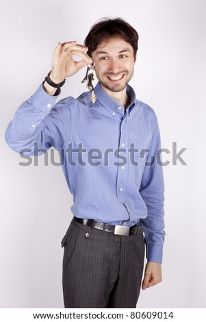 handsome young man stands and holds the keys to a new apartment - stock photo