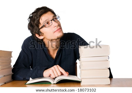 Handsome young man studying and dreaming between stacks of books on table. - stock photo