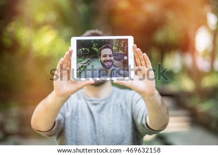 handsome young man taking a selfie with a tablet, smiling. graded with a flare, in instagram style.