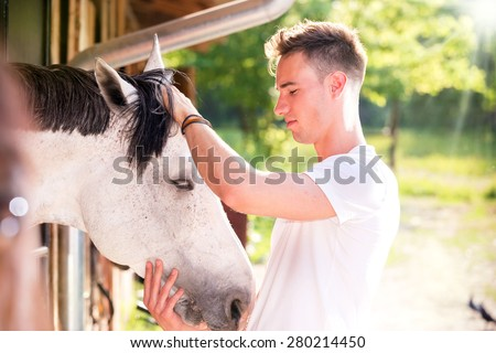 Handsome young man taking care of him white horse. Lens Flare - stock photo
