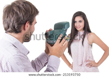 Handsome young man taking photos of beautiful model with instant camera isolated on white