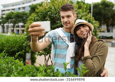 Handsome young man taking selfie with his beautiful girlfriend - stock photo